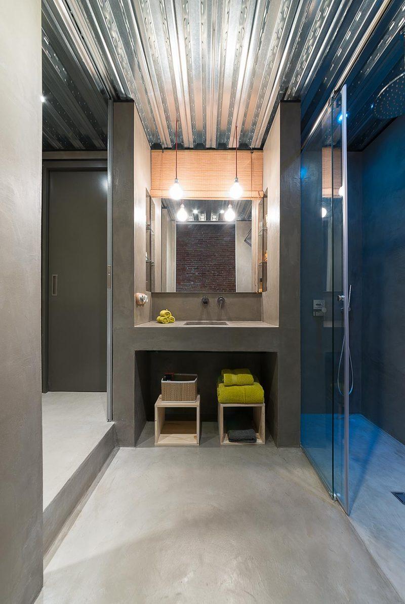 De stoere betonlook gietvloer past perfect in deze industriële badkamer, ontworpen door Studio FFWD.