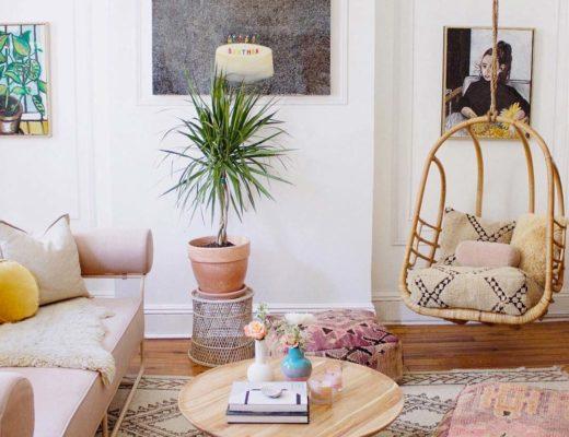 bohemian stijl woonkamer met rotan hangstoel, kleurrijke kussens en planten