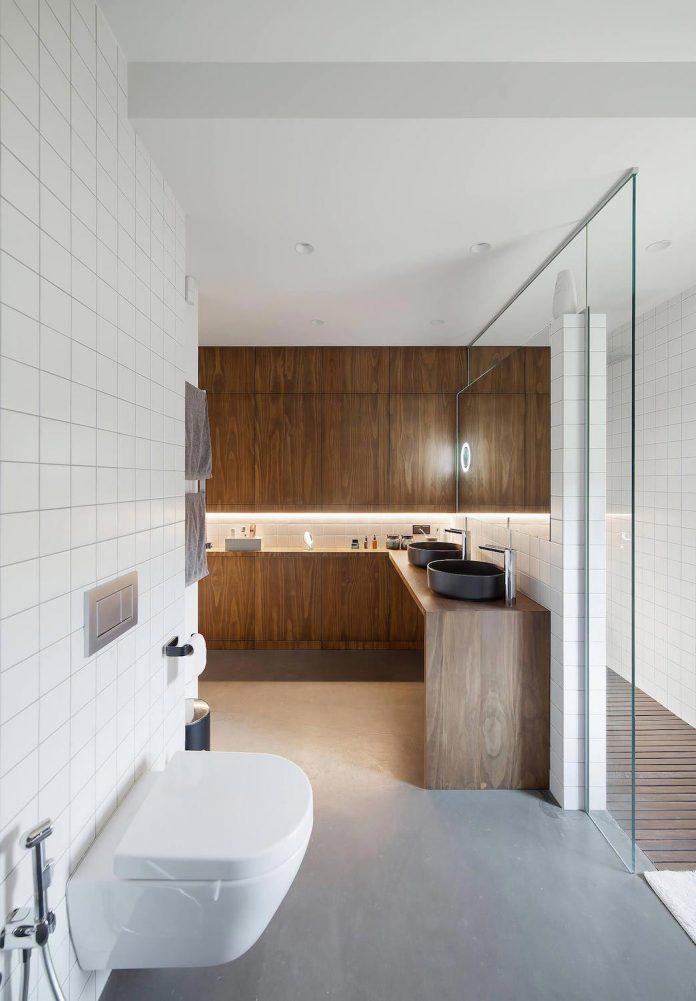 De cementgebonden gietvloer en de houten kasten vormen een prachtige combinatie in deze mooie badkamer ontworpen door Oekraiense architecten bureau Tseh Architectural Group.