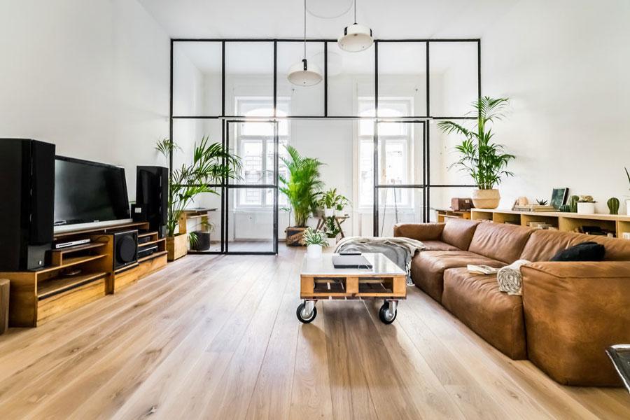 In deze woonkamer hebben ze een grote glazen scheidingswand met stalen kozijnen geplaatst om er een aparte werkplek te creëren. Klik hier om meer foto's te bekijken.