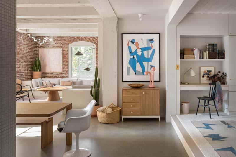 Het grote kunstwerk boven de houten dressoir valt op dankzij de mooie kleuren. Klik hier om meer foto's te bekijken van deze super mooie woonkamer.