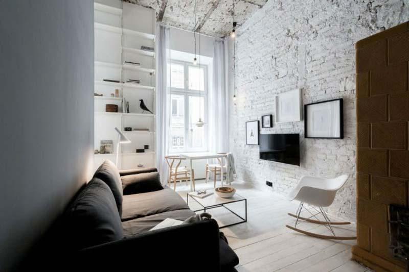 De grote witte bakstenen muur in deze stoere woonkamer is een leuke collage gecreëerd rondom de TV. Klik hier voor meer foto's.