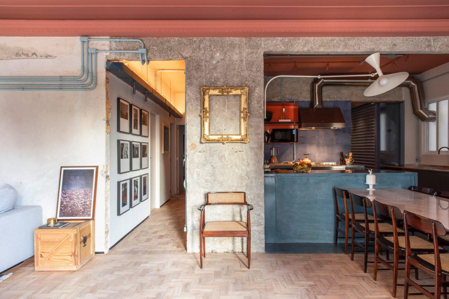 In dit stoere appartement uit São Paulo is een eclectische keuken ontworpen met een schiereiland waar een grote eettafel aan gemonteerd is.