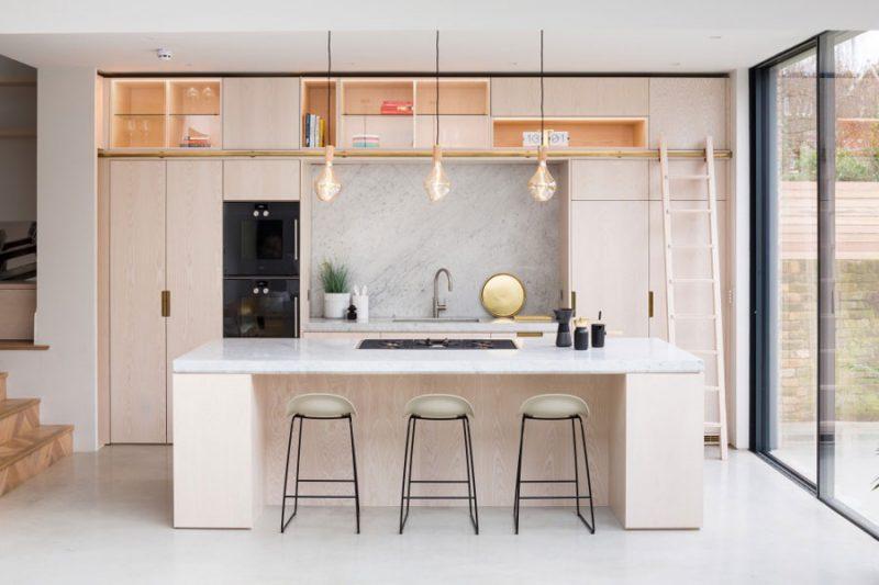 In de uitbouw van een Victoriaanse woning in Londen is er gekozen voor een super mooie lichtgrijze gietvloer, die perfect staat bij de houten keuken met kookeiland.