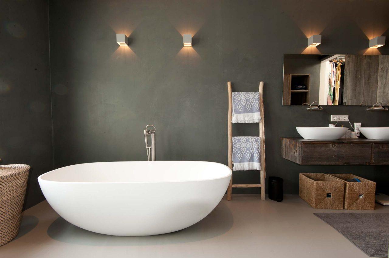 MARC archtitects heeft deze moderne rustieke badkamer ontworpen, waar een strakke PU gietvloer gecombineerd is met donkergrijze betonstuc wanden.