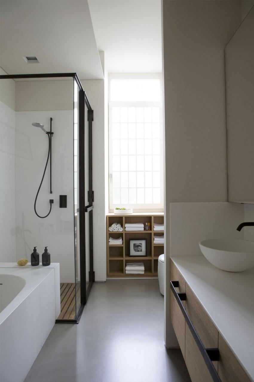 De lichte gietvloer in deze moderne badkamer vormt een perfecte combinatie met de houten onderdelen en het zwarte industriële staal - ontworpen door ontwerper Fabio Fantolino.