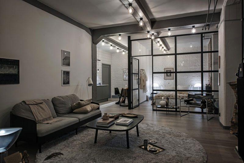Stoere industriële woonkamer met een groot rond vloerkleed in de zithoek.