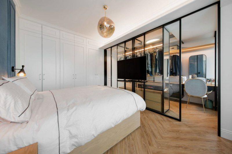 Grote glazen wand en deuren met stalen kozijnen scheiden hier de inloopkast van de slaapkamer