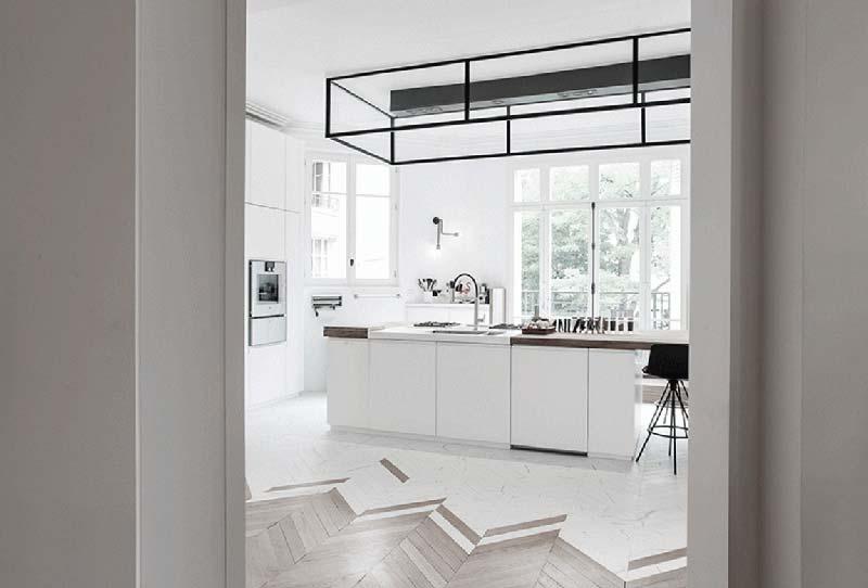 In de Hongaarse punt vloer van deze mooie keuken lopen de houten planken over op witte marmeren tegels.