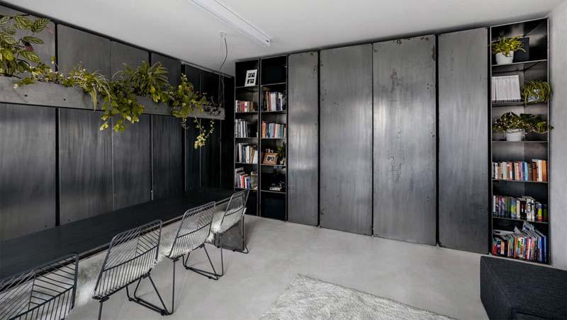 In dit mini industriële loft appartement vind je stoere stalen details, zoals de op maat gemaakte boekenkast, de wanden en de industriële hanglamp boven de eettafel.