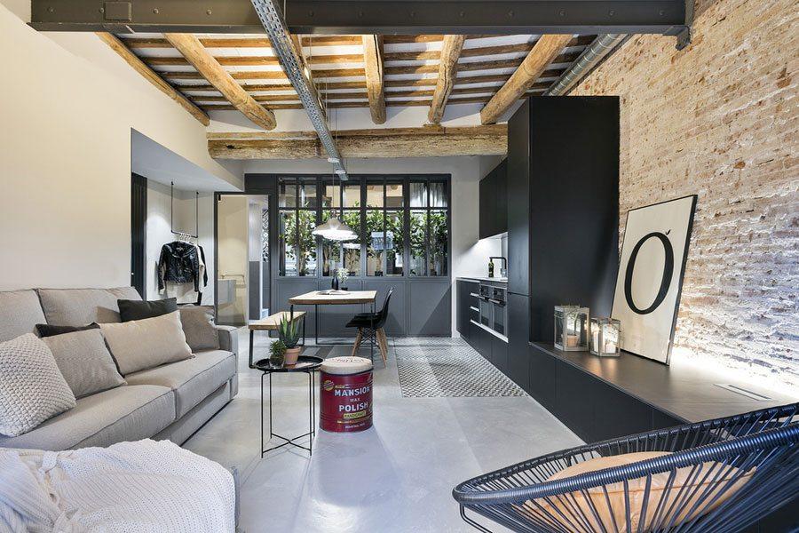 De bakstenen muur is een echte blikvanger in deze moderne industriële woonkamer, ontworpen door Dröm Living