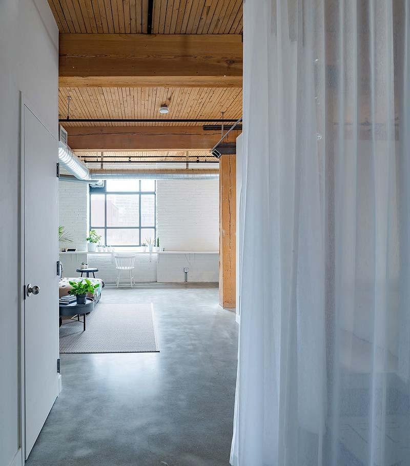 In het Broadview loft appartement is er gekozen voor een stoere betonlook gietvloer, gecombineerd met wit geverfde bakstenen muren en warm houten plafond.