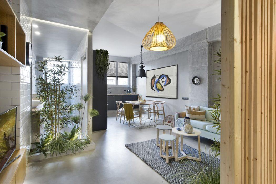 Interieurontwerp studio Egue Y Set koos voor een combinatie van betonlook muren, betonlook vloer en metrotegels aan de wand in deze industriële woonkamer.