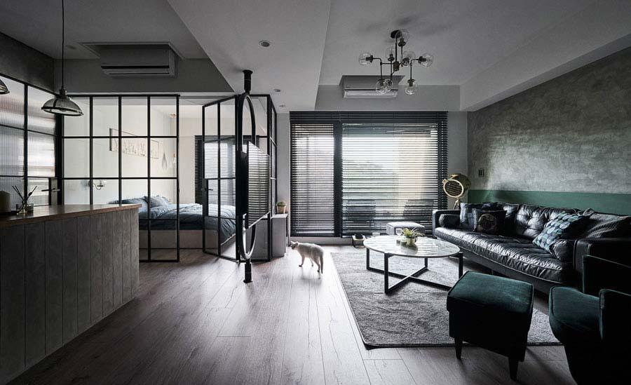 Interieur- en ontwerpbureau White Interior Design Studio heeft hier de woonkamer en de slaapkamer van elkaar gescheiden met glazen wanden en bijpassende stalen deur.