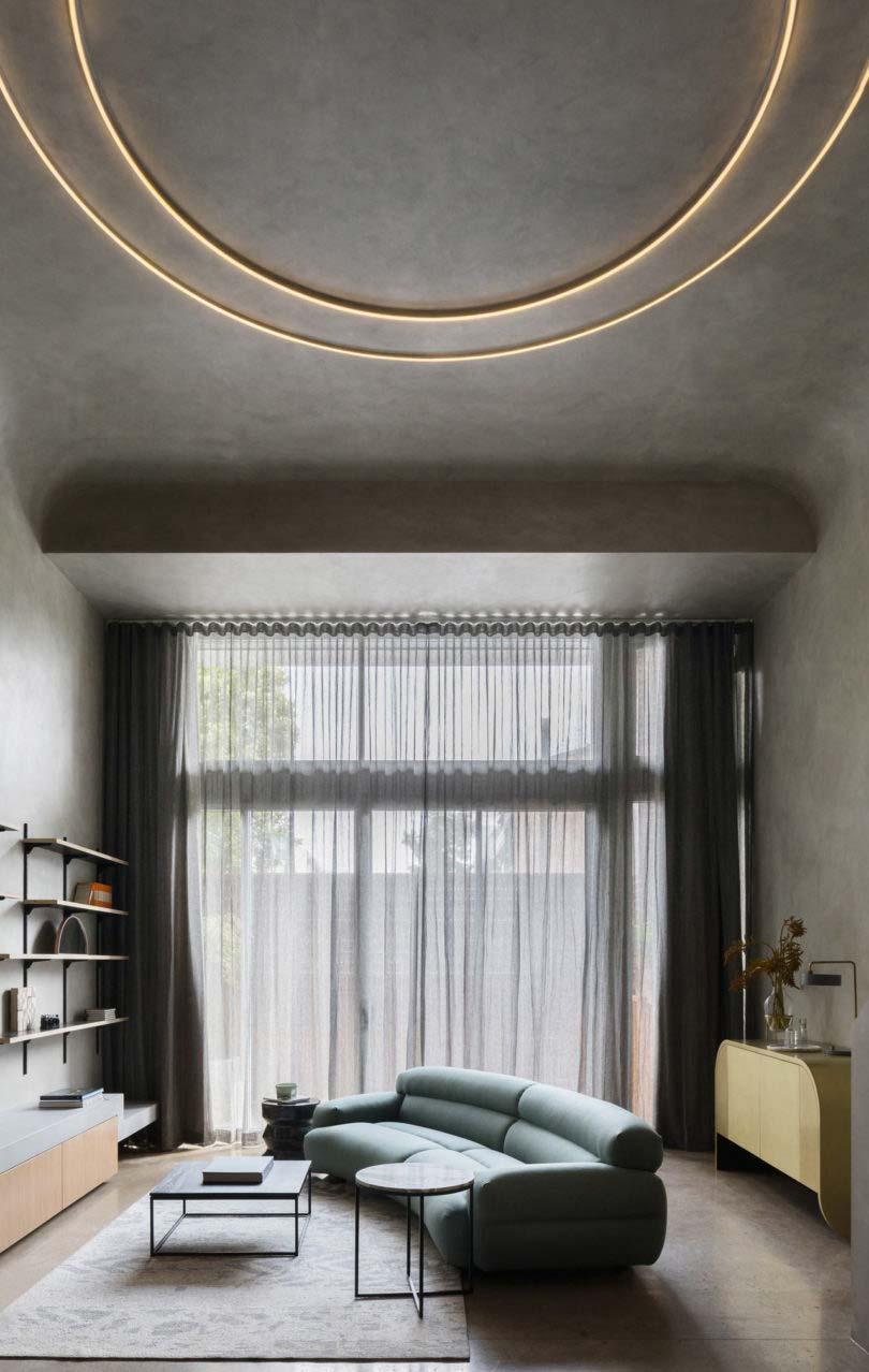 In deze stoere woonkamer met betonlook wanden en plafond, heeft interieurontwerper Matt Woods gekozen voor een hele bijzondere wandlamp.