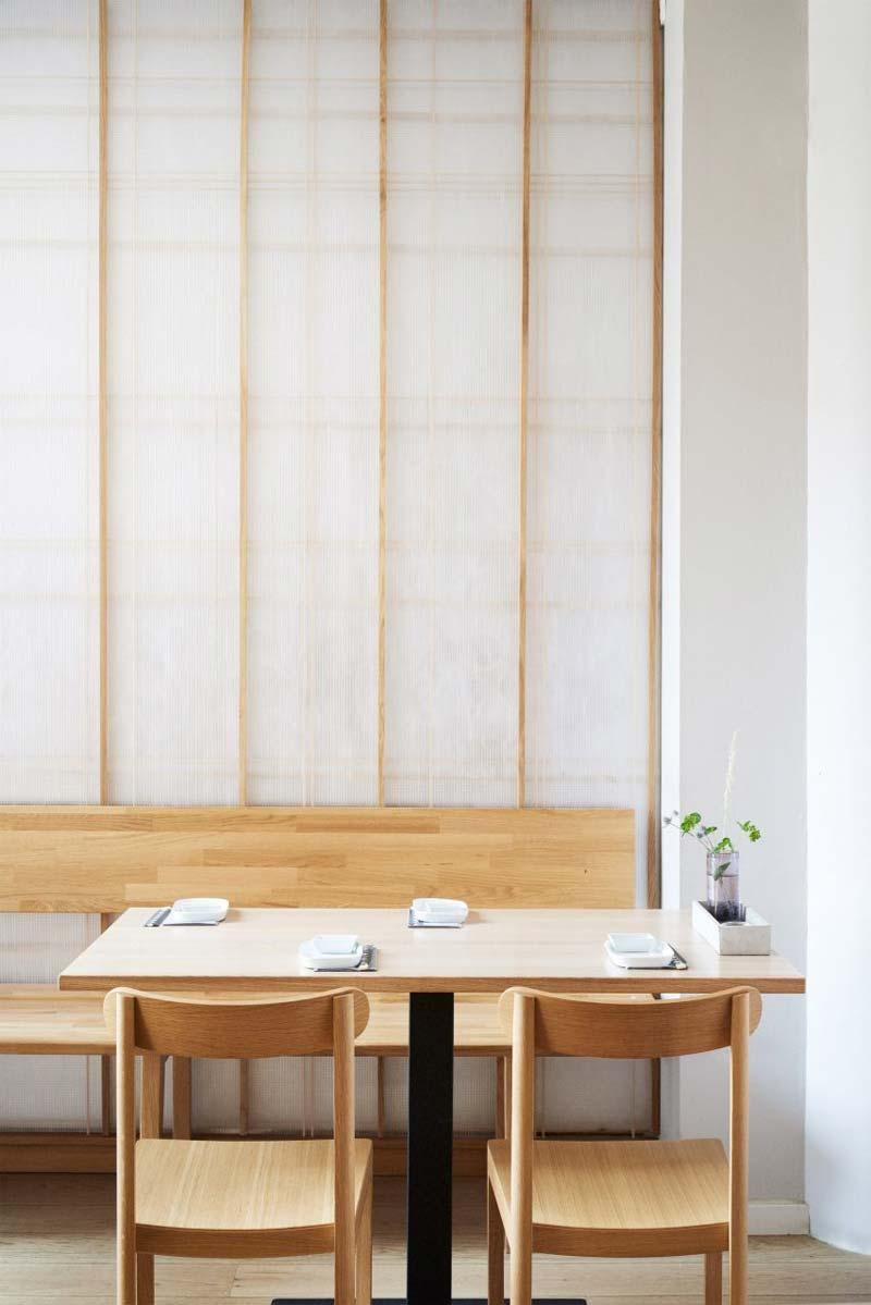 """Een Japans restaurant in Kopenhagen is de perfecte setting voor een interieurstijl die de twee culturen combineert.  Izumi, in de buitenwijk Charlottenlund van de stad, put uit beide Japanse restaurantinterieurs, met doorschijnende schermen die verwijzen naar traditionele papieren schuifdeuren, en Scandinavisch design. Dit is te zien aan de gebogen eikenhouten panelen die de open keuken omringen.  """"Japan en de Noordse landen hebben een rijke geschiedenis van culturele interacties"""", aldus de oprichters van Pan-Projects, Yurioko Yaga en Kazumasa Takada. """"Vooral op het gebied van design zijn er veel voorbeelden die oorspronkelijk geworteld zijn in de Japanse cultuur, maar zich op unieke wijze hebben ontwikkeld in het land van de Scandinavische regio."""""""