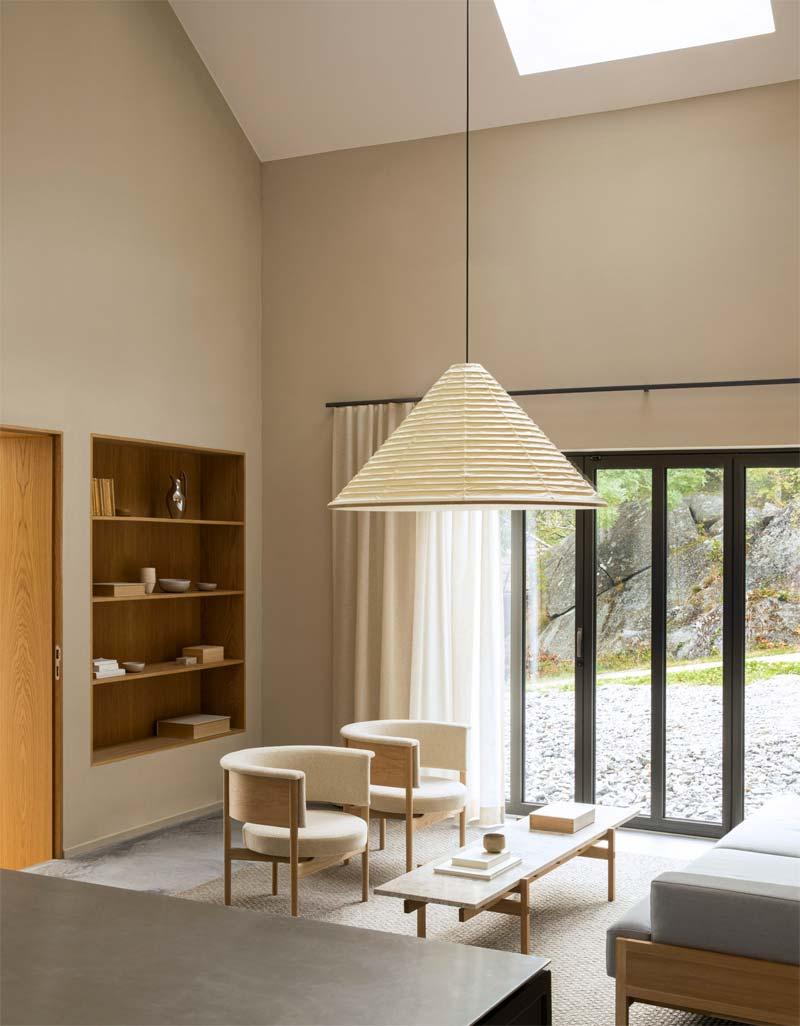 Norm Architects 'Archipelago House is een met dennenhout bekleed vakantiehuis dat is ontworpen om de Zweedse en Japanse esthetiek te belichamen, een thema dat het duidelijkst naar voren komt in de dubbelhoge woonkamer. Hier kunnen de eigenaren loungen op meubels die Norm Architects ontwierp samen met Karimoku Case Study - het zustermerk van de Japanse fabrikant Karimoku. Crèmewitte en lichtgrijze tinten vormen een aanvulling op de lichte houten meubels in de kamer, waar de belangrijkste lichtbron een op maat gemaakte kegelvormige lantaarn is. Dit is ontworpen in washi-papier door de Japanse Kojima Shouten, die al meer dan 230 jaar lantaarns maakt.
