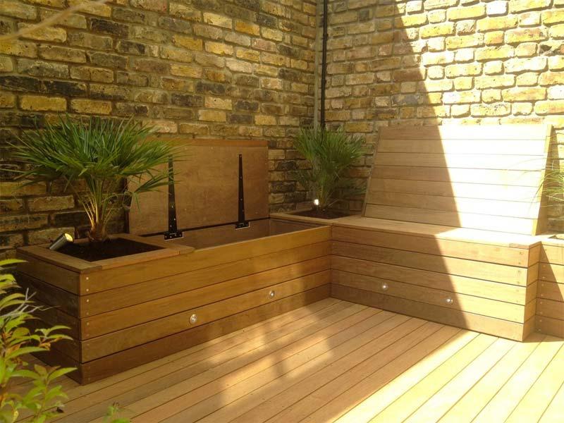 De op maat gemaakte houten bank in deze kleine tuin bevat niet alleen opbergruimte, maar ook leuke vaste plantenbakken.