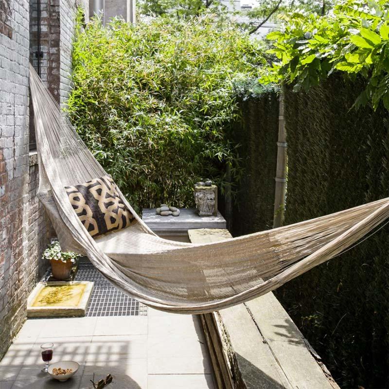 Deze tuin is weliswaar klein en smal, maar dit weerhoudt de eigenaren niet om er een heerlijke ligplek te creëren, door een hangmat op te hangen.
