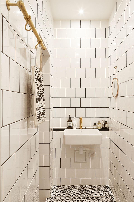 Kleine witte badkamer met gouden details