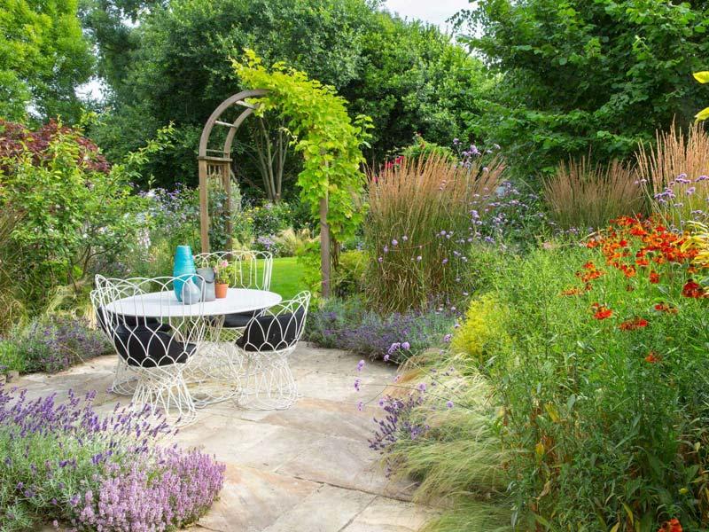 landelijke tuin ronde tafel mooie beplanting