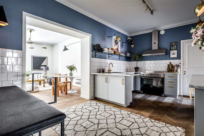 In deze chique keuken met lichtgrijze kasten, marmeren werkblad en gouden deurgrepen, is er gekozen voor een korte schiereiland met extra kastruimte en werkruimte.