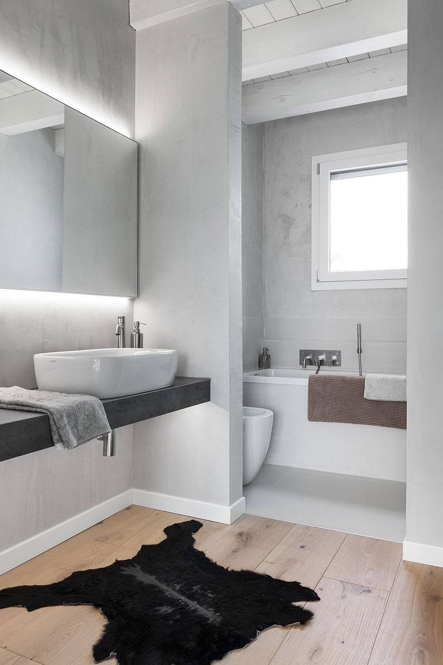 Ook in deze badkamer, ontworpen door Anna Laura Businaro, is er gekozen voor een strakke gietvloer in het natte gedeelte en een houten vloer in het droge gedeelte.
