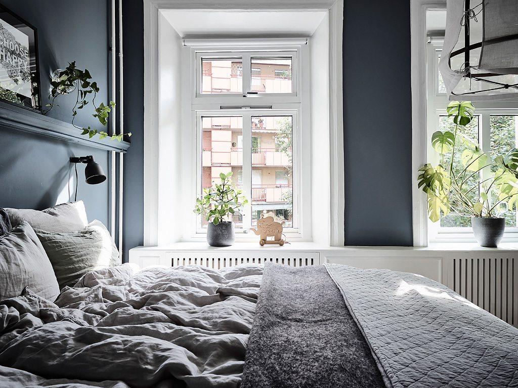 In deze mooie slaapkamer zijn gordijnen opgehangen vóór de open kledingkast