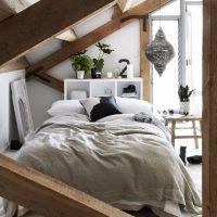 Bed onder schuin dak op zolder slaapkamer