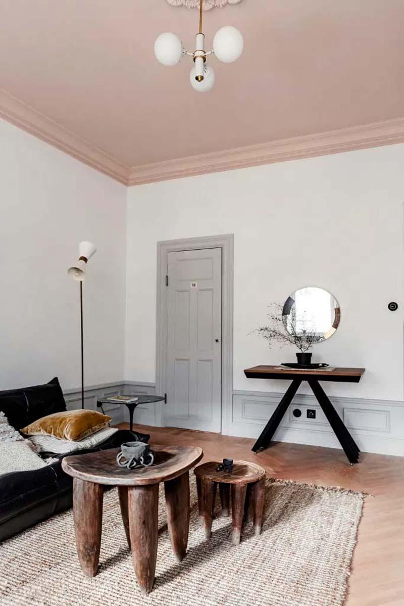 Mooie karakteristieke woonkamer met roze plafond, witte muren, lichtgrijze deur, jute vloerkleed en boomstam tafeltjes
