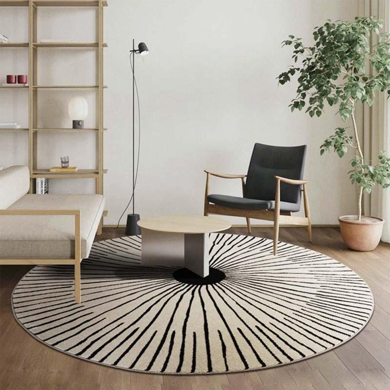 Groot rond vloerkleed met een print in een kleine woonkamer.