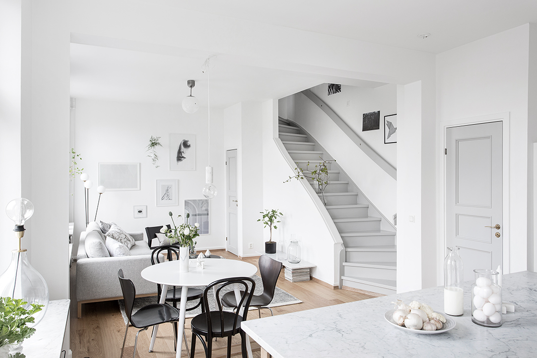 ruimtelijke woonkamer met open keuken en trap inrichting