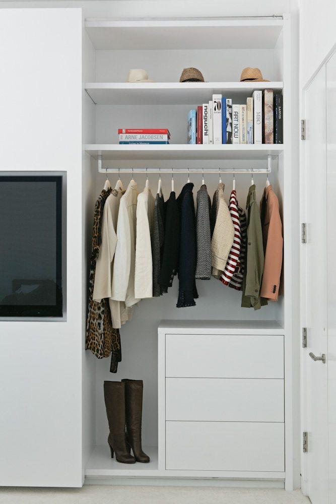 In de schuifdeur van deze strakke slaapkamer inbouwkast is de TV verwerkt!