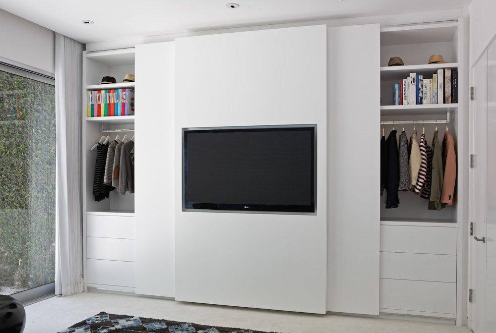 in de schuifdeur van deze strakke slaapkamer inbouwkast is de tv verwerkt