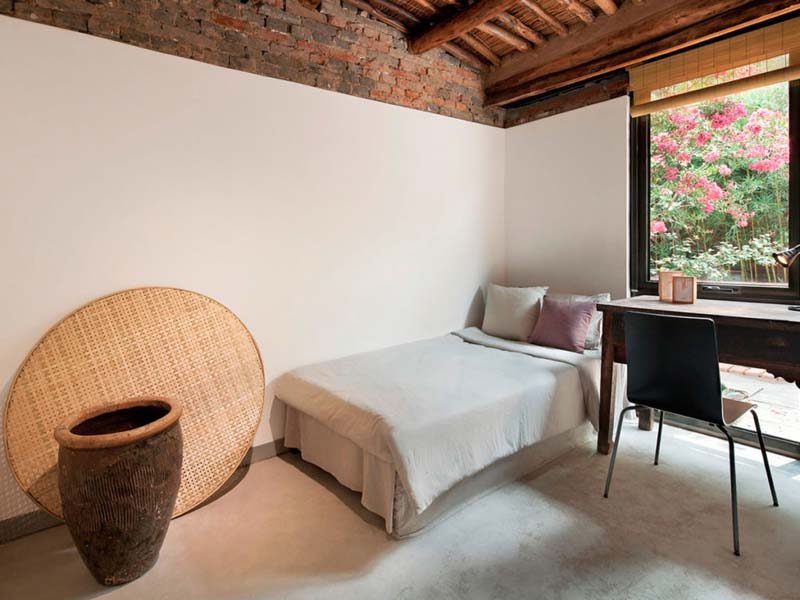 slaapkamer betonvloer bakstenen muur stucen