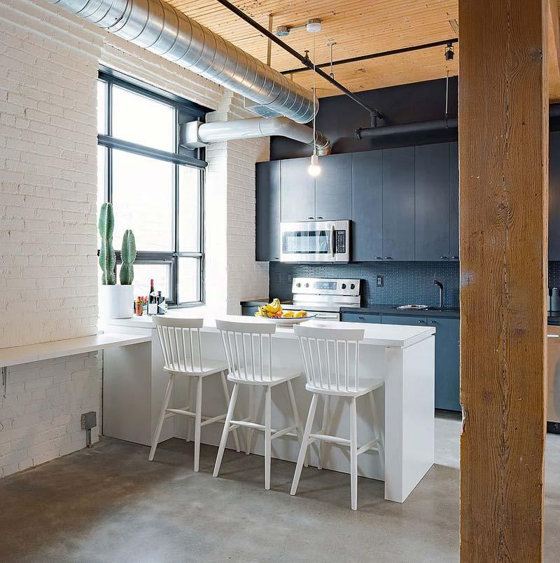 In dit kleine loft appartement is gekozen voor een open schiereiland keuken met drie mooie bijpassende witte barkrukken.