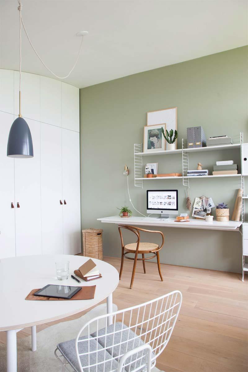 Mooi thuiskantoor met groene muur - verlichting in de vorm van gouden wandlamp en hanglamp