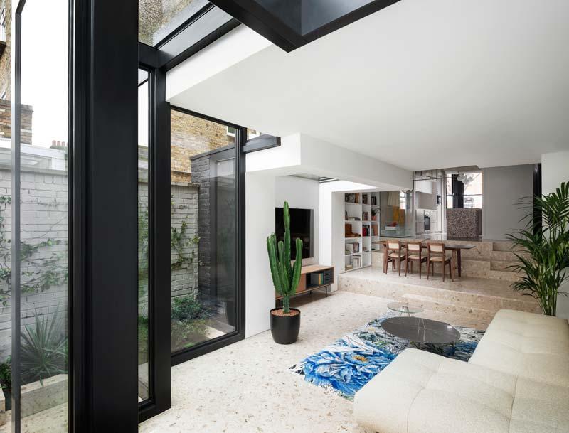 trapvormige glazen uitbouw splitlevel woonkamer keuken