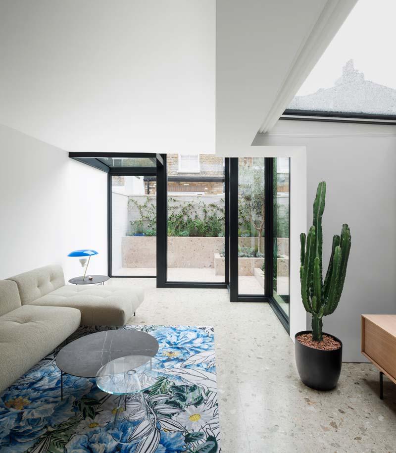 trapvormige glazen uitbouw woonkamer