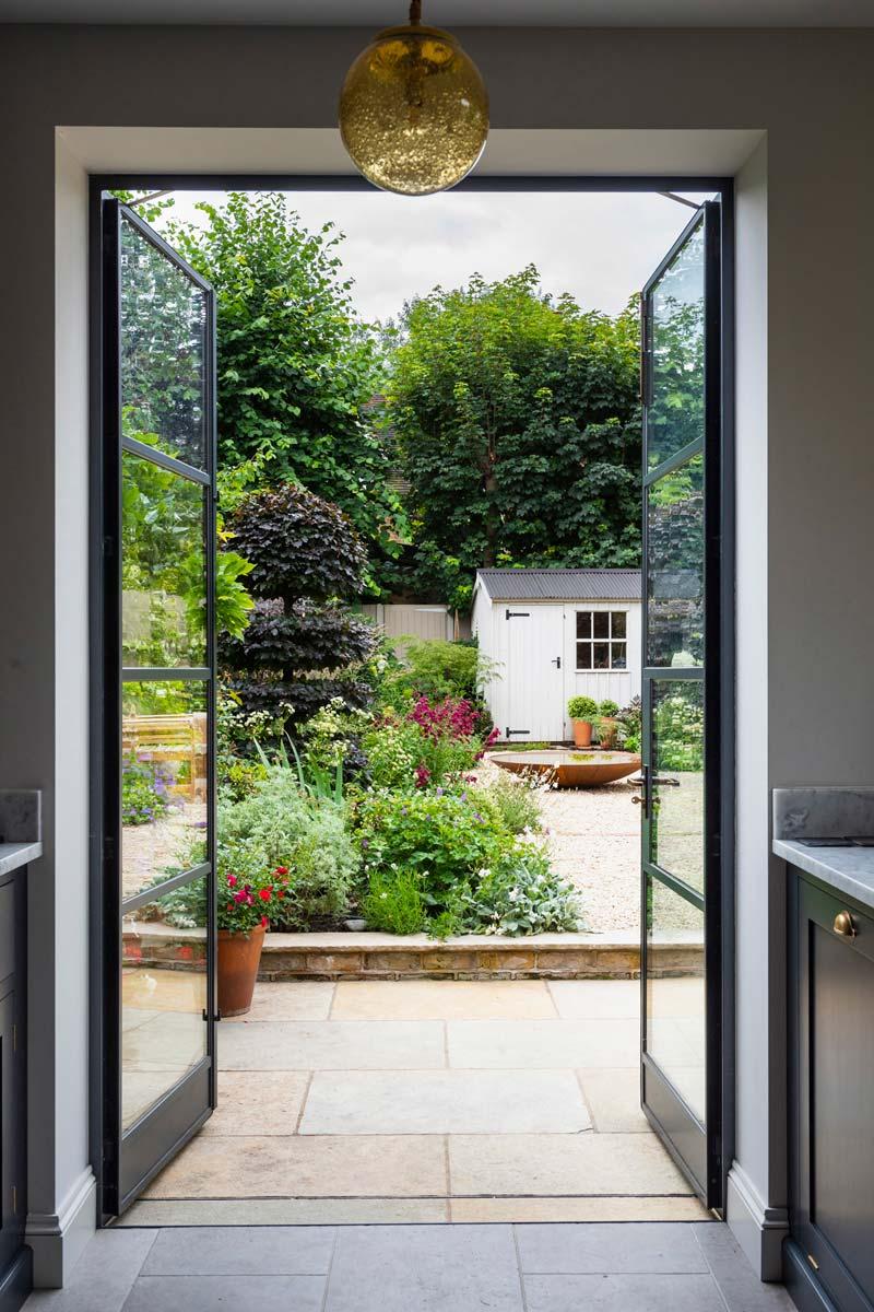 tuin voorbeelden grindtuin openslaande stalen deuren vanuit keuken
