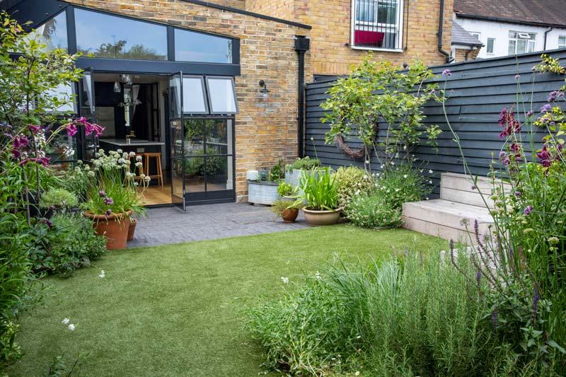 tuin voorbeelden kindvriendelijke tuin zwarte potdekselen schutting