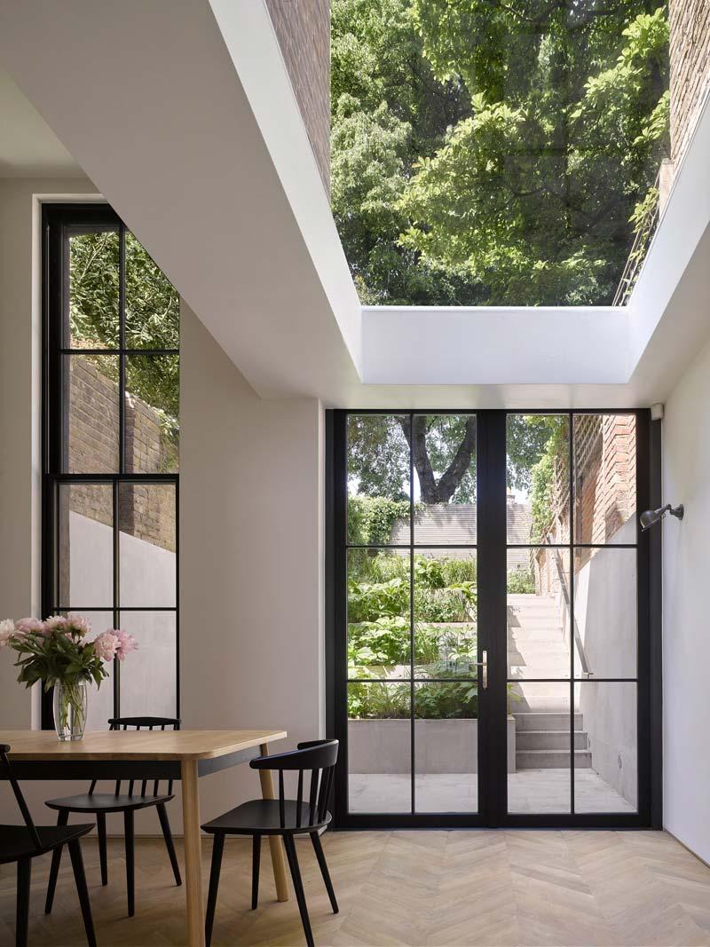 verticale uitbouw stalen achterpui met glazen deuren en dak