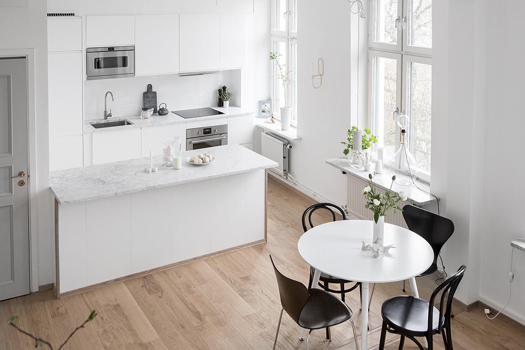 Aan deze ruimtelijke woonkamer is een hele fijne open witte keuken ingericht met een groot schiereiland met marmeren werkblad.