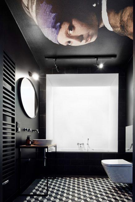 Zwarte badkamer met beroemd kunstwerk aan plafond